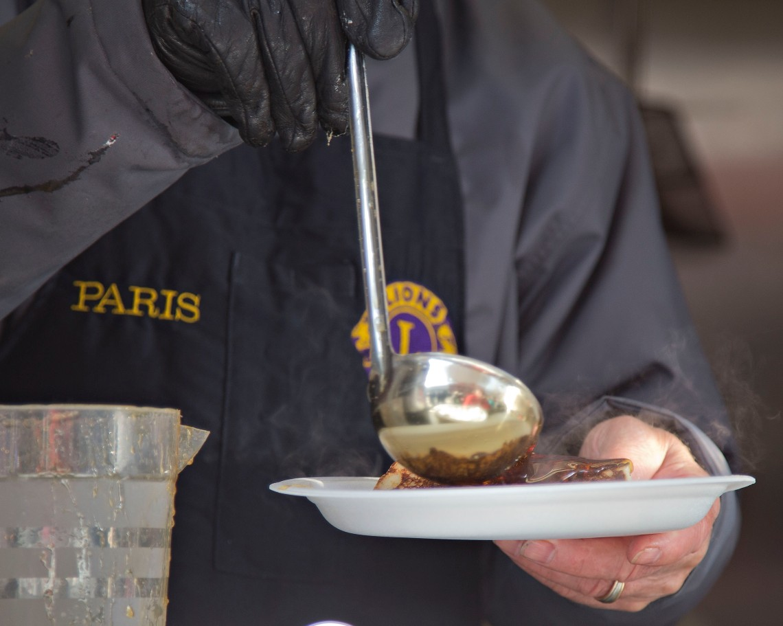 Man serving food at the Paris Maple Syrup Festival