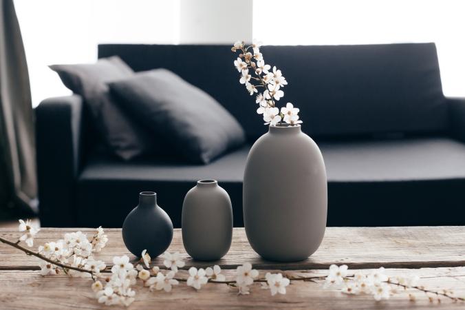 Minimalistic home decor on rustic coffee table over black sofa w